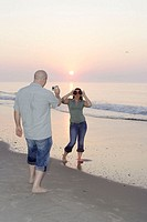 Couple in their 20´s having fun on the beach of ocean city taking pictures during sunrise/sunset, she plays with donuts as glasses