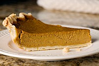 Food. Riverwoods, Illinois. One slice of homemade pumpkin pie and crumbs on white plate white napkin on granite counter top