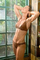 Young woman in brown bathing suit rinses off in shower.