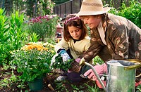 Senior woman planting flowers in garden with her granddaughter.
