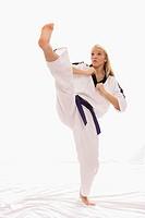 young woman practice a karate high kick
