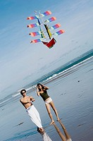couple playing kite on beach