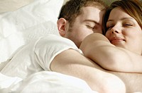 Young couple in bed cuddling together
