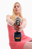 Young girl in her 20´s holding a power tool/ drill in her hand pointing to the camera