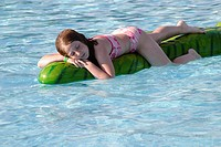 10-year-old girl in pink-and-white two-piece swimsuit lying contentedly on a floating plastic animal in a public swimming pool, in sunshine -- Bloomin...
