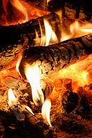 detail of fire in fireplace, glowing coals, yellow-white flames at ends of logs and in embers
