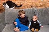 Three_year_old and three_month_old on the couch with cat looking on.