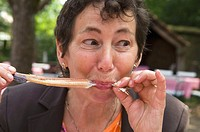 Woman 60-65 years old eating a smoked eel in an outdoor restaurant North Germany