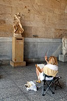 Designer in front of a statue in the Ancient Agora Museum (Stoa of Attalos), Athens. Greece