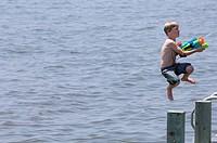 boy shooting water gun while jumping into the Albemarle Sound, North Carolina