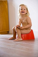 Blond little girl is sitting on a potty