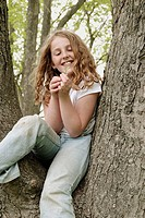 Preteen girl with wavy gold-brown hair and freckles, sitting in tree, in faded jeans and white short-sleeved top, looking at small white wildflower an...
