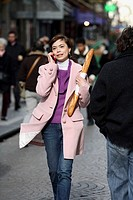 A young woman holding a baguette and talking on her cell phone on the street of Paris. Paris. France.