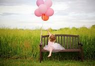 Girl, age 3 looking at balloons. In Illinois at farm. Hay feild.