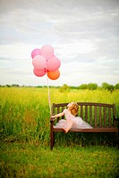 Girl, age 3 looking at balloons.