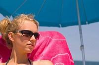 Young woman enjoying sitting at the beach under an umbrella. Sandbridge Beach, Virginia Beach, Virginia, USA