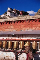 Prayer wheels along outer wall of Potala Palace, Lhasa. Tibet, China