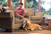 Man reading on chair with dog on floor next to him