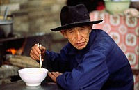 Old man eating noodle soup, Xichuangbanna, Yunnan, China