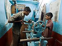 Laborers, including a child, using machine in a shop in Bangalore, Karnataka, India