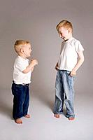 Two blond haired brothers, 6 and 3 years old, wearing white t-shirts and blue jeans, look at each other and laugh, sharing a joke. Studio lighting, gr...