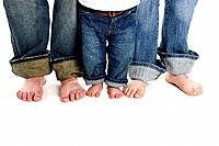 A family of three, mother, father and toddler son, stand on a white background wearing jeans. Only their legs and bare feet are shown.