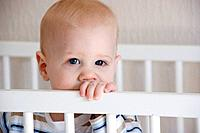 A young fair-haired, blue-eyed baby boy stands in his white crib, looking at the camera.
