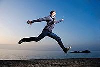Young man jumping along the seashore at dawn