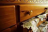 USA money spilling out drawer.