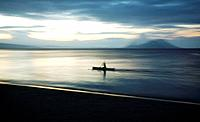 Tavurvur Volcano in the distance, a fisherman rows offshore near the town of Kokopo which has since become the main town for East New Britain since th...