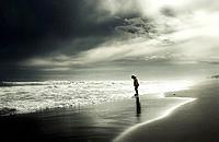 Joven paseando solo por la orilla del mar en invierno.