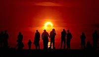An annular solar eclipse in progress graces the sky at Dog Beach in San Diego, California, USA