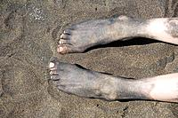 Spain. Canary islands. Gran Canaria. Las Palmas. Las Canteras beach. Volcanic sand on feet.