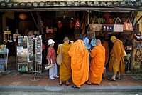 Group of male buddist monks, accompained by a tourist guide, shopping souvenirs in Hoi An, the best preserved town of Vietnam.