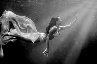 Girl swimming underwater, searching for the light.