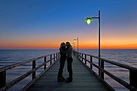 Young couple on sea bridge kissed at sunrise, Island Usedom, Baltic sea, Mecklenburg Vorpommern, Germany