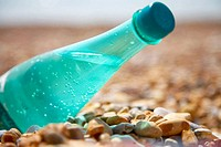Green plastic bottle of mineral water on a beach