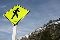 Yellow road sign: pedestrian crossing and mountain range of Milford Sound, Fiordland NP, South Island, New Zealand