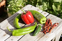 Red bell pepper & red & green chilis on weathered outdoor table.