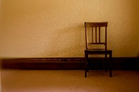 Wooden chair against wall.