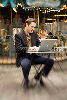 Man working outside in a park, typing on laptop and talking on cell phone in front of carousel.