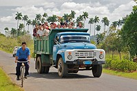 A dump truck full of people passing a man riding a bicycle.