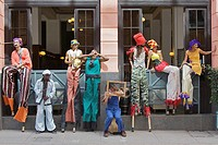 A group of street performers on stilts taking a break.
