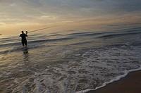 Man fishing at sunrise on Malvarrosa beach, Valencia city, Valencia, Comunidad Valenciana, Spain, Europe