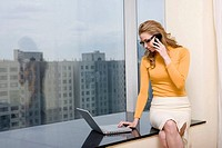 Young businesswoman sitting in front of laptop using mobile phone