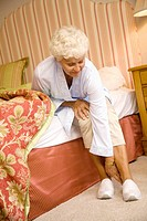 Elderly woman putting her slippers on