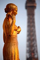 Closed up view of a gilded bronze statues on the central square of the Palais de Chailot with Eiffel Tower in background, Paris. France