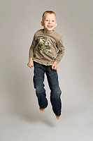 Blonde-haired, blue-eyed six year old boy in studio, jumping and smiling against a pale grey background. He wears jeans and a long-sleeved t-shirt.