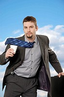 Businessman running with coffee and briefcase with serious expression He looks determined and focused