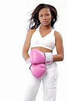 Young fit woman in sports bra and workout pants, wearing boxing gloves and looking intently at the viewer